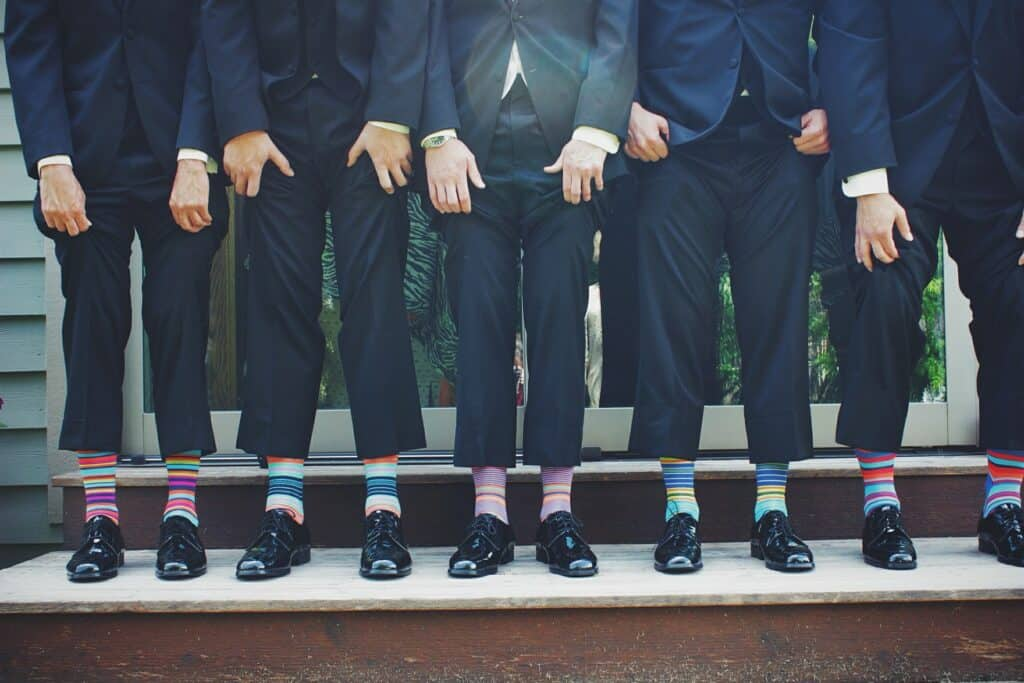 Men in formal wear showing off their colored socks