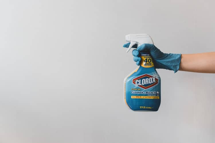 Person holding a spray of bleach to clean yellow soles