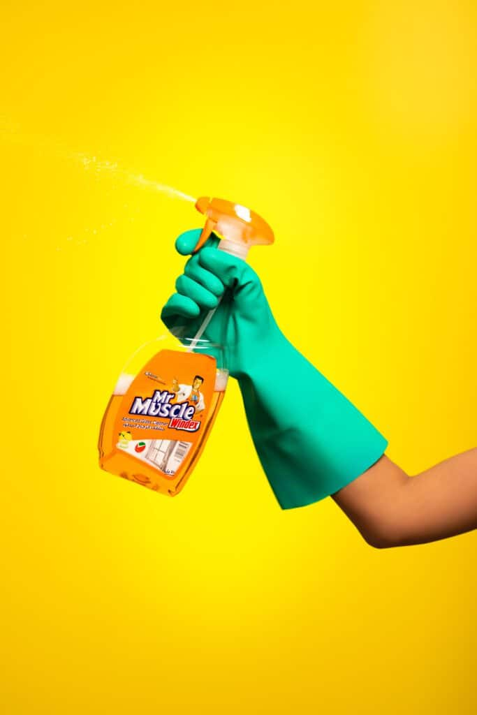Person holding a Windex spray