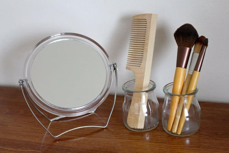 Mirror, clean wooden comb, and brushes in a table
