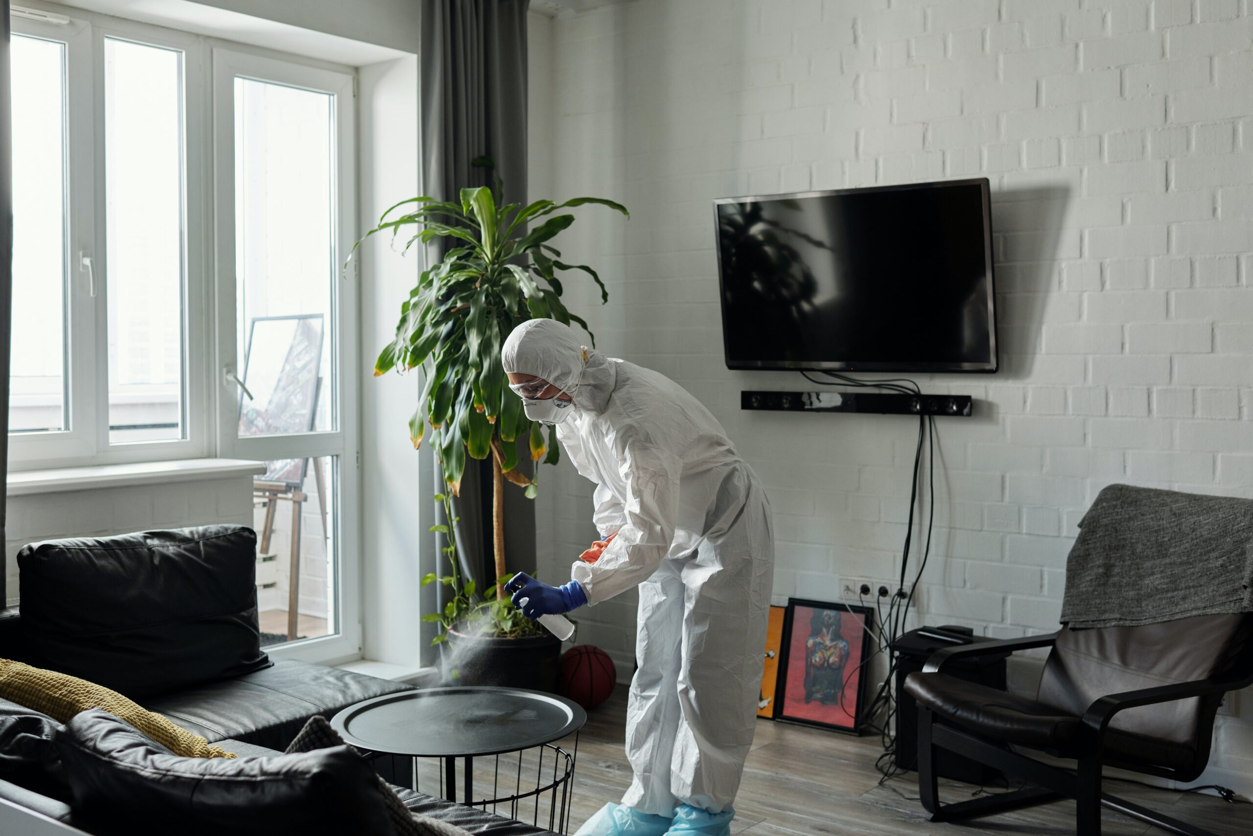 A person using a disinfectant and wearing protective equipment while cleaning