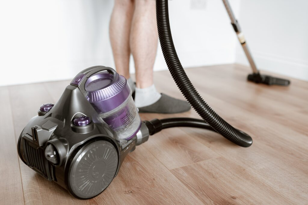 A c;lose up shot of a purple vacuum cleaner being used