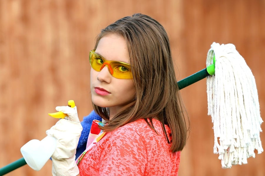Woman holding a mop and a cleaning solution spray for floors