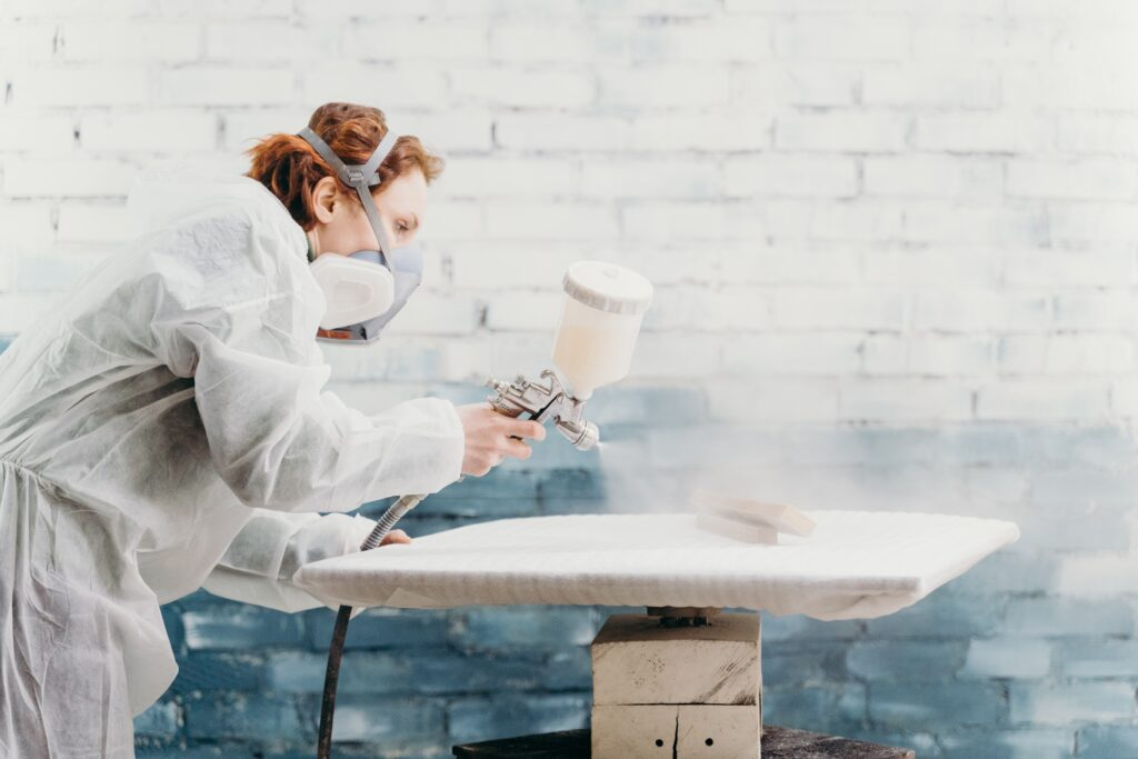 A person using a spray paint gun with a white color