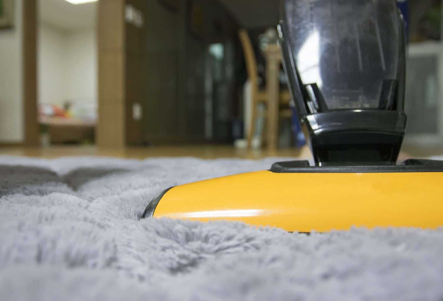 A close up shot of a yellow vacuum cleaner on a rug