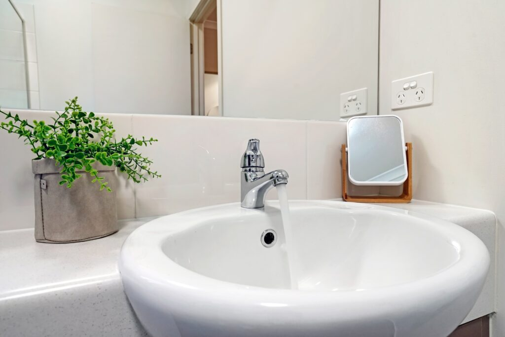 A bathroom sink with running water and a sink overflow
