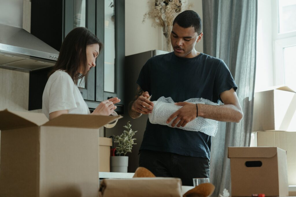 Two persons organizing things with boxes and wrap