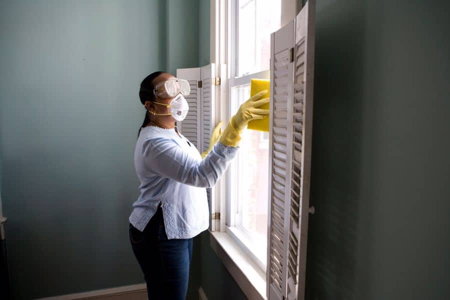 Woman cleaning a double hung window that don't tilt