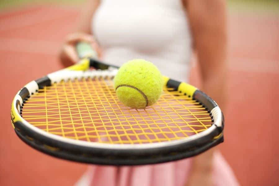 Person holding a racket with tennis ball