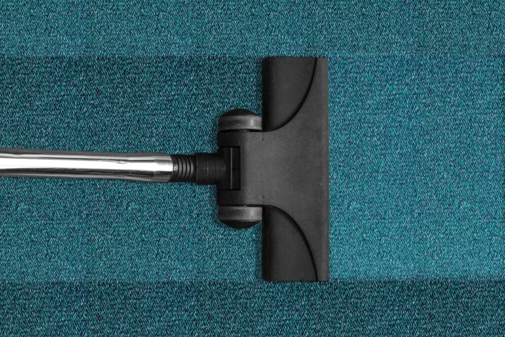 Removing dust and dirt on a blue carpet with a cleaner