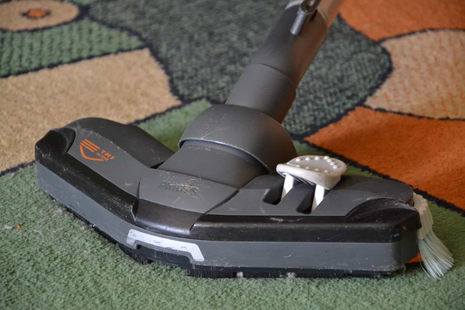 A carpet cleaner with brushes on a multi-toned carpet