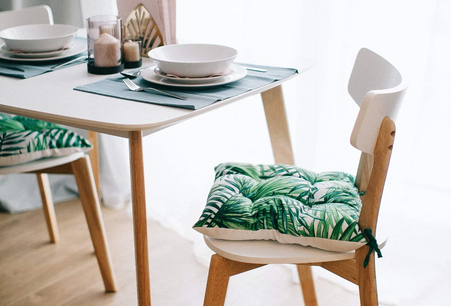 A wooden dining table with a dining chair and a separate cushion