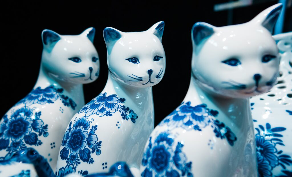Porcelain figurines of cats with blue marks