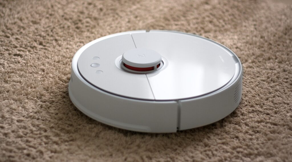 A white robot vacuum on a rug