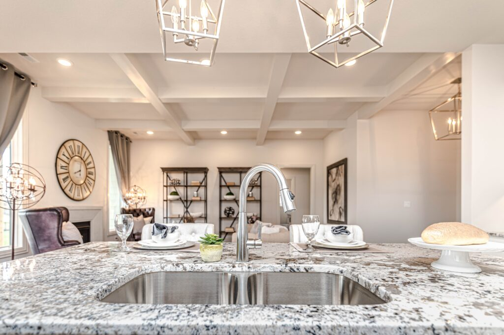 A marble kitchen countertop with plates and a sink