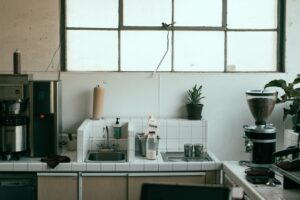 A messy kitchen countertop with white small tles and coffeemaker