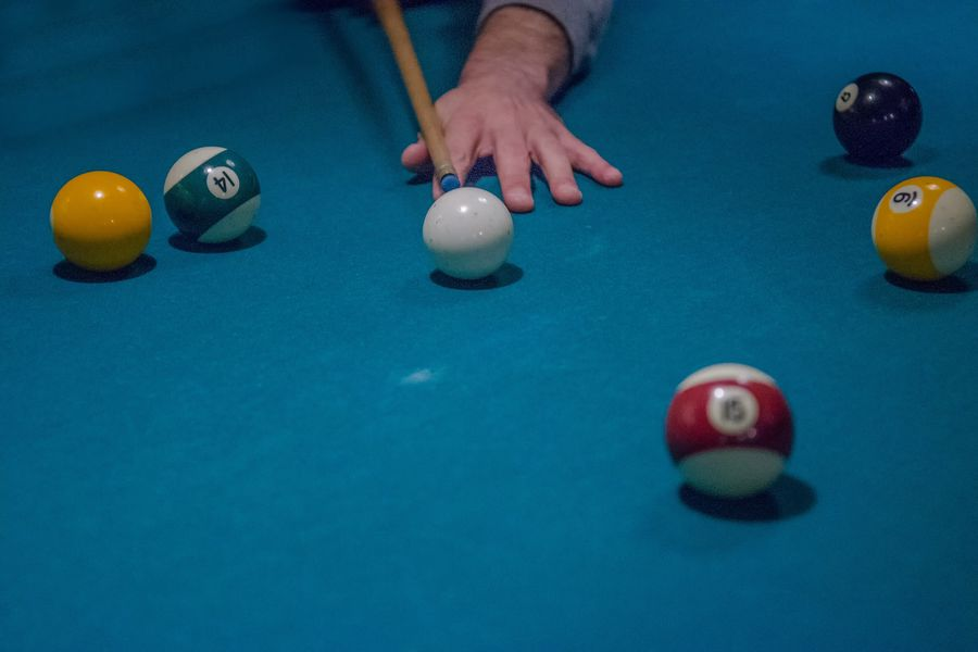 Person aiming the cue stick to hit a ball