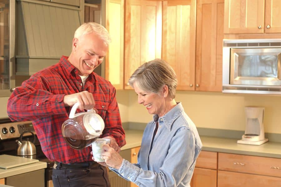 Man pours coffee for a woman while standing in the kitchen