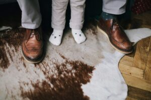 Closeup of people's feet stepping on a clean cowhide rug