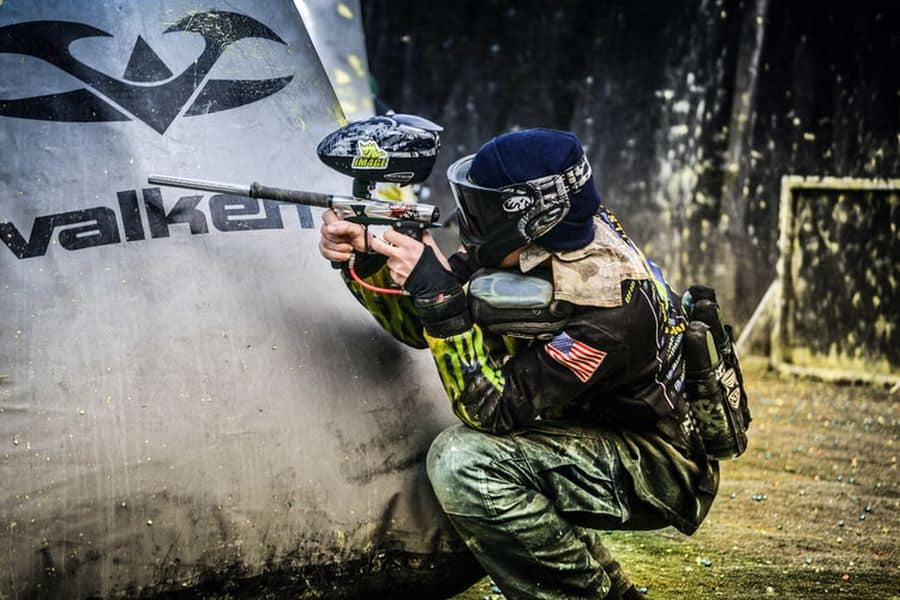 Person holding a paintball gun in the middle of a game