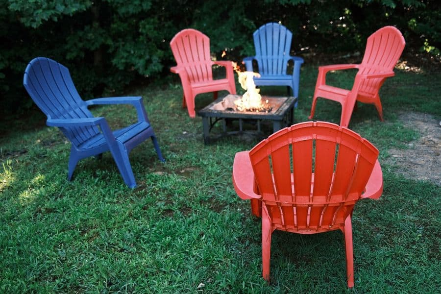 Red and blue plastic lawn chairs surrounding a fire pit