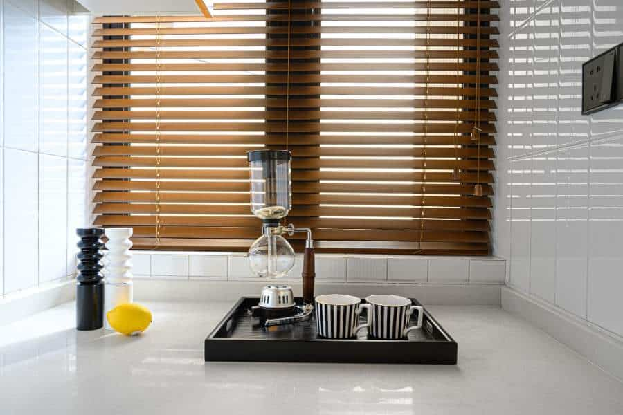 Window with faux wood blinds near a kitchen corner