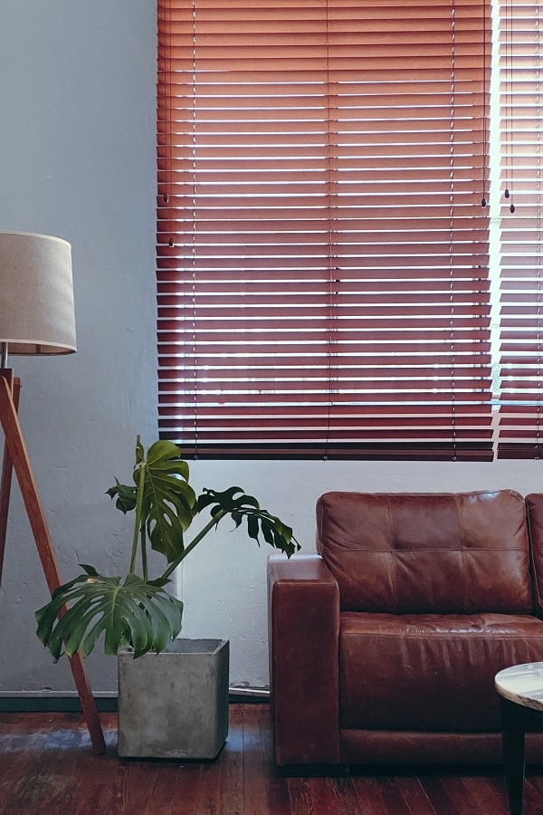 Faux wood blinds behind a leather couch