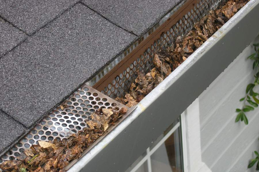 A roof gutter filled with dried leaves
