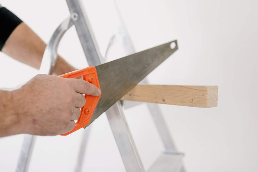 A person using a hand saw to cut a piece of wood