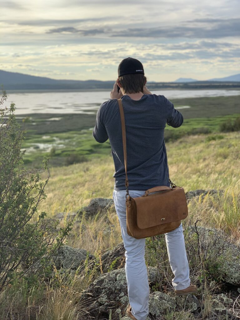 Man taking a photo of the landscape while carrying his thrifted leather purse