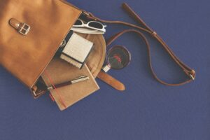 Perfume, notebook, wallet, ballpen and a sunglass are spilling out of a leather purse