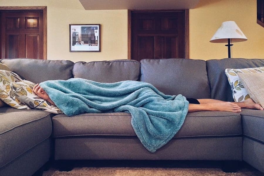 Person sleeping underneath a blanket in a couch