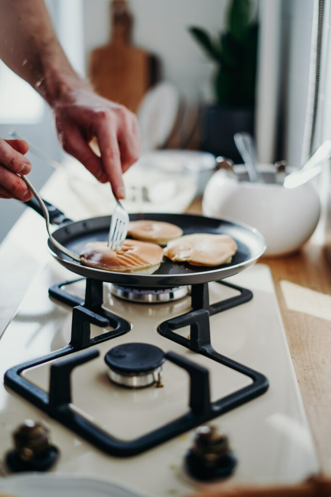 Person cooking pancakes with a stovetop griddle