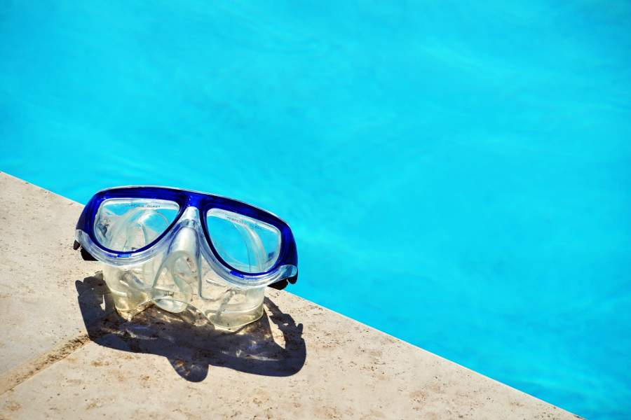A snorkel mask beside the pool