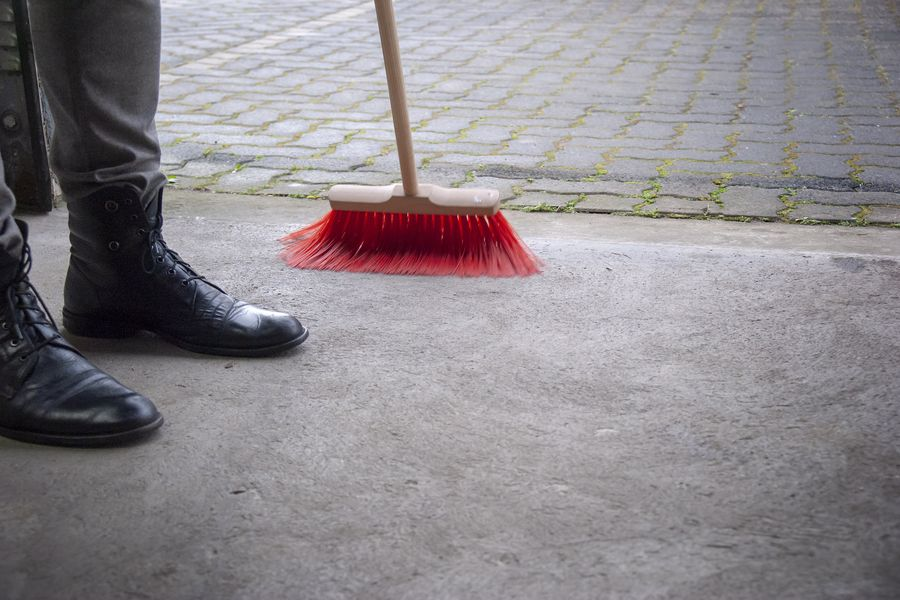 Person sweeping the pavement