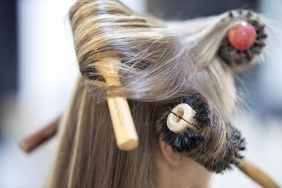 Three brushes rolled into a woman's hair