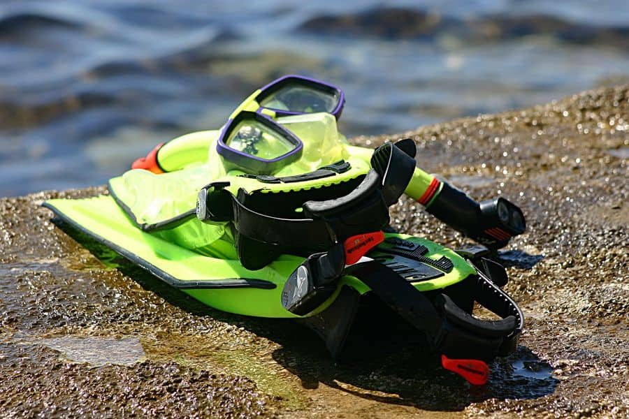Complete snorkel gear laid out in the beach rocks